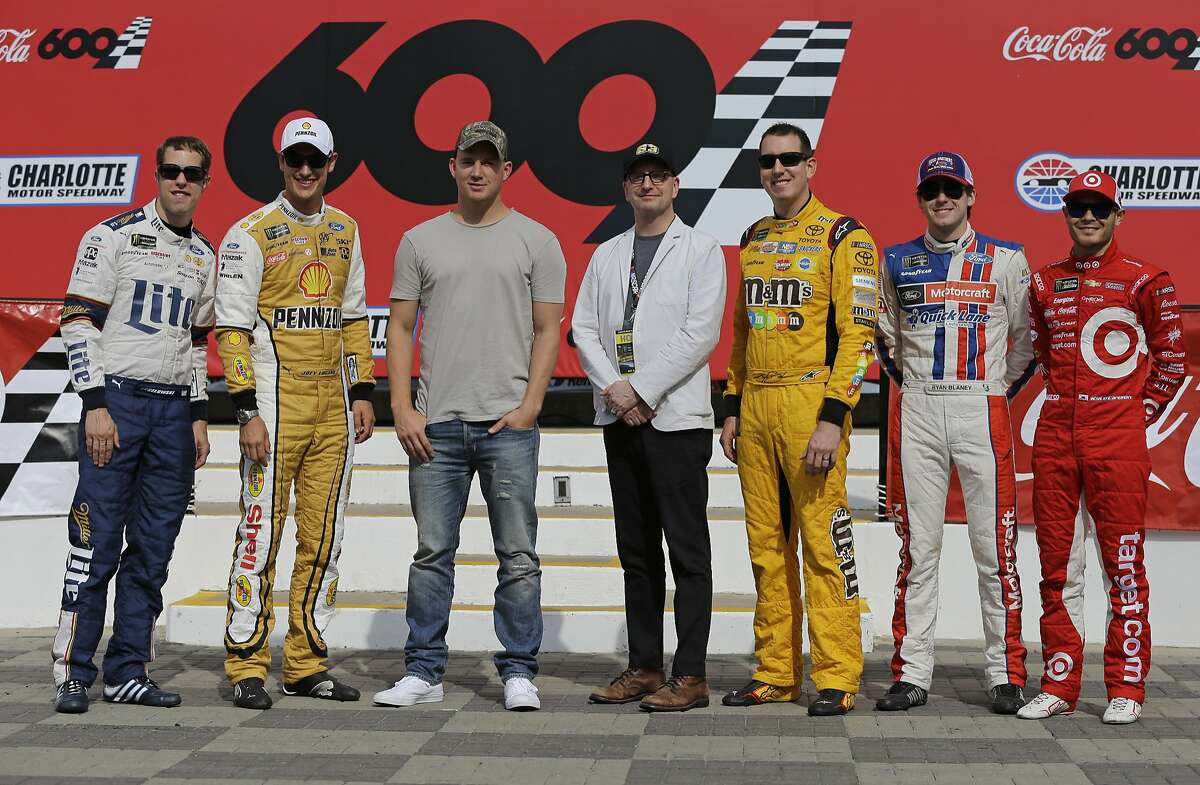 """Actor Channing Tatum, third from left, and director Steven Soderbergh, center, pose for a photo with NASCAR drivers, from left to right, Brad Keselowski, Joey Logano, Kyle Busch, Ryan Blaney and Kyle Larson before the NASCAR Cup series auto race at Charlotte Motor Speedway in Concord, N.C., Sunday, May 28, 2017. Tatum and the drivers will star in a new movie filmed at the speedway named """"Logan Lucky,"""" and directed by Soderbergh. (AP Photo/Chuck Burton)"""