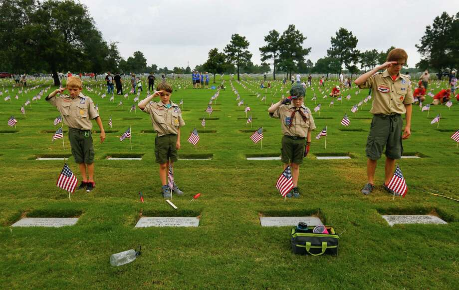 Cypress scouts Brenden, Lyle, Danial and Bradley (who declined to give their last names) stand back and salute the graves where they just placed American flags at Houston National Cemetery in preparation for Memorial Day, Sunday, May 28, 2017, in Houston. Volunteers were instructed to place the flags exactly one foot in front of each grave, stand back and read the person's name out loud and thank them for their service. Many volunteers would salute when they did this. (Annie Mulligan / For the Houston Chronicle) Photo: Annie Mulligan, Annie Mulligan / Houston Chronicle / 2017 Annie Mulligan / Houston Chronicle