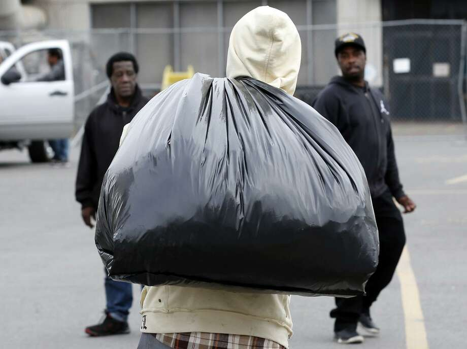 James White carries a bag of his possessions toward co-workers Barry Thomas (left) and Eric Lee after the last of the laid-off employees made a final visit to the shipyard at Pier 70. Photo: Paul Chinn / Paul Chinn / The Chronicle / ONLINE_YES