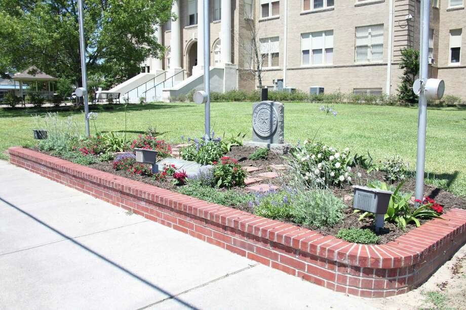 The flower bed in front of the Coldspring courthouse rests in front of memorials to Master Sergeant Merritt Truman Lilley and to veterans of all wars. Nan Kittel volunteered her time to take care of it and spoke before the San Jacinto County Commissioners Court on May 23 and explained her concerns about certain requests not being fulfilled to help her prepare the gardenfor Memorial Day. Photo: Jacob McAdams