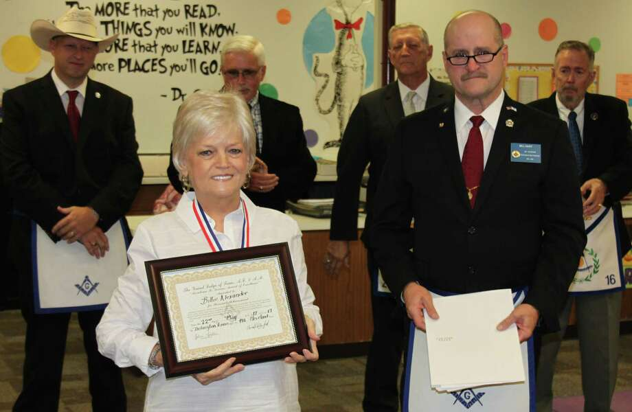 Billie Alexander (left) receives the Mirabeau B. Lamar award from Tarkington Prairie Lodge Senior Warden Bill Hart (right) in honor of teaching three generations of students at Tarkington Primary in both math and art. Alexander received the award on May 22. Photo: Jacob McAdams