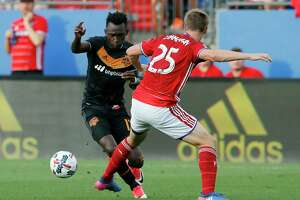Houston Dynamo's Alberth Elis, left, loses control of the ball against FC Dallas's Walker Zimmerman, right, in the first half of an MLS soccer game, Sunday, May 28, 2017, in Frisco, Texas. Zimmerman was injured on the play and left the game with an unknown injury. (AP Photo/Tony Gutierrez)