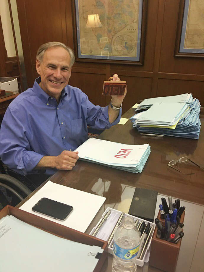 "Texas Governor Greg Abbott smiles from his desk as he wields a ""Veto"" stamp as he looks through bills in his Capitol office, Sunday night, May 28, 2017. Photo: Mike Ward / Houston Chronicle / 2017 Mike Ward / Houston Chronicle"