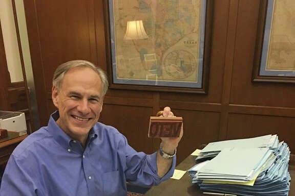 """Texas Governor Greg Abbott smiles from his desk as he wields a """"Veto"""" stamp as he looks through bills in his Capitol office, Sunday night, May 28, 2017."""