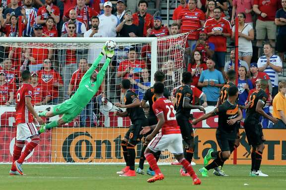 Dynamo goalkeeper Tyler Deric stretches out to make a save on a free kick by FC Dallas in the first half Sunday night in Frisco.