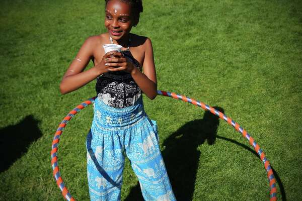 Zariyah Quiroz, 10, multitasks with a hula hoop and sno-cone during the 2017 Northwest Folklife Festival at Seattle Center, Sunday, May 28, 2017.