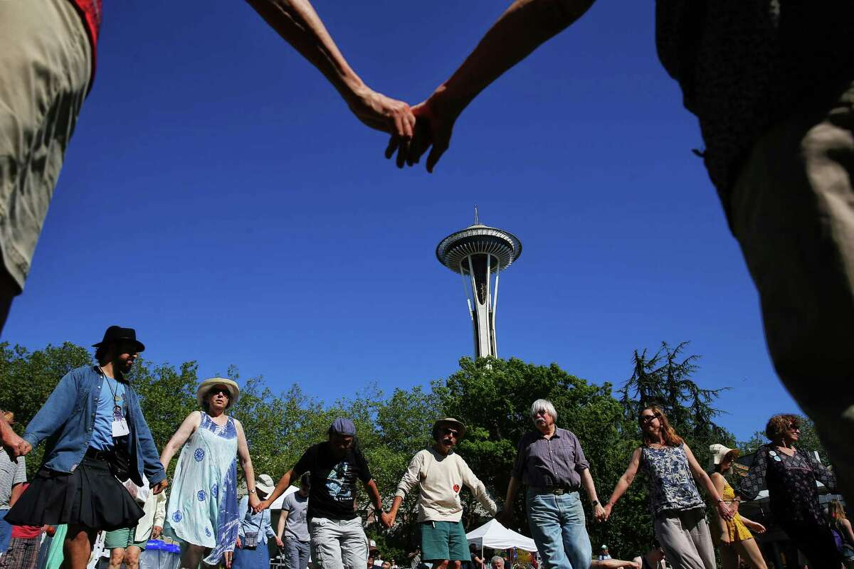 People dance in a circle as bands play during the 2017 Northwest Folklife Festival at Seattle Center, Sunday, May 28, 2017.