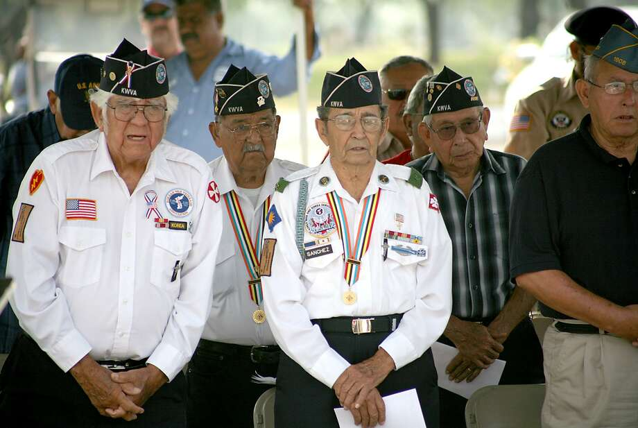 Veterans rise in prayer during a ceremony in commemoration of fallen soldiers led by Bishop James Tamayo at the Calvary Catholic Cementery on Saturday morning. Photo: Francisco Vera, Staff Photographer / Laredo Morning Times / Laredo Morning Times
