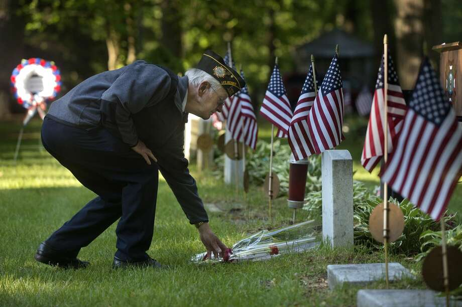 David Patrick with the Veterans of Foreign Wars Chemical City Post 3651 places a red carnation on a grave during a service at the Midland Cemetery on Memorial Day. Photo: Brittney Lohmiller/Midland Daily/Brittney Lohmiller