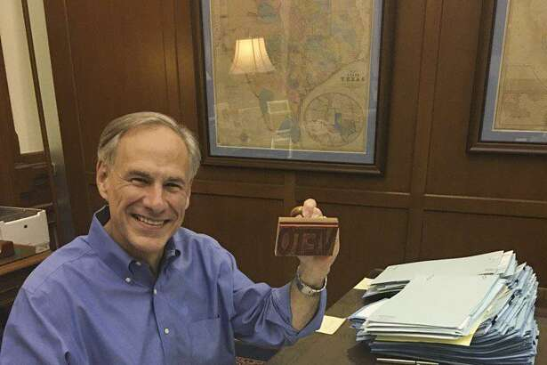 """Gov. Greg Abbott smiles from his desk as he wields a """"Veto"""" stamp as he looks through bills in his Capitol office Sunday. Abbott said Monday that he will announce later this week whether he's going to call a special session so the Legislature can take up bills it failed to approve during the regular session."""