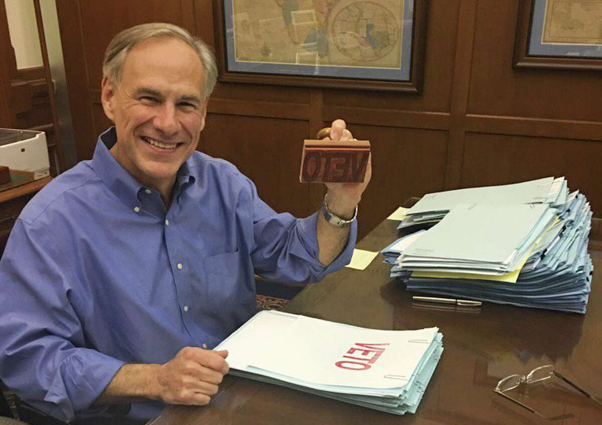 """Texas Governor Greg Abbott smiles from his desk as he wields a """"Veto"""" stamp as he looks through bills in his Capitol office, Sunday night, May 28, 2017. He signed more bills Wednesday but still isn't ready to reveal any plans he has for any special sessions."""
