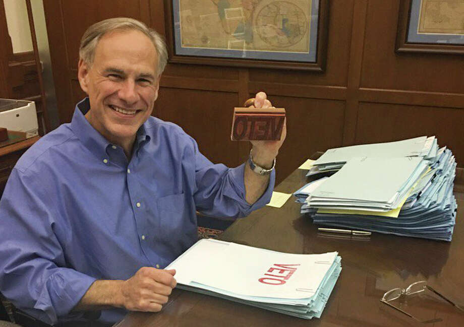 """Texas Governor Greg Abbott smiles from his desk as he wields a """"Veto"""" stamp as he looks through bills in his Capitol office, Sunday night, May 28, 2017.  / 2017 Mike Ward / Houston Chronicle"""