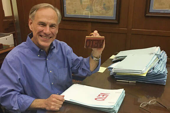 "Texas Governor Greg Abbott smiles from his desk as he wields a ""Veto"" stamp as he looks through bills in his Capitol office, Sunday night, May 28, 2017."