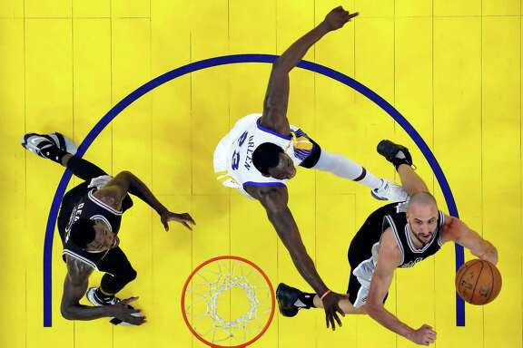 Manu Ginobli tries to put up a shot against Draymond Green (23) in in game 2 of the Western Conference Finals against the Golden State Warriors. The Spurs lost the series in four games, and there is talk about whether Ginobli will retire. A reader says he knows how the beloved forward can remain on the team.