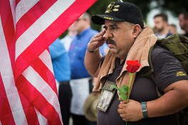 Daniel Martinez, a U.S. Army veteran pays his respects on Memorial Day at the Houston National Cemetery, Monday, May 29, 2017, in Houston.