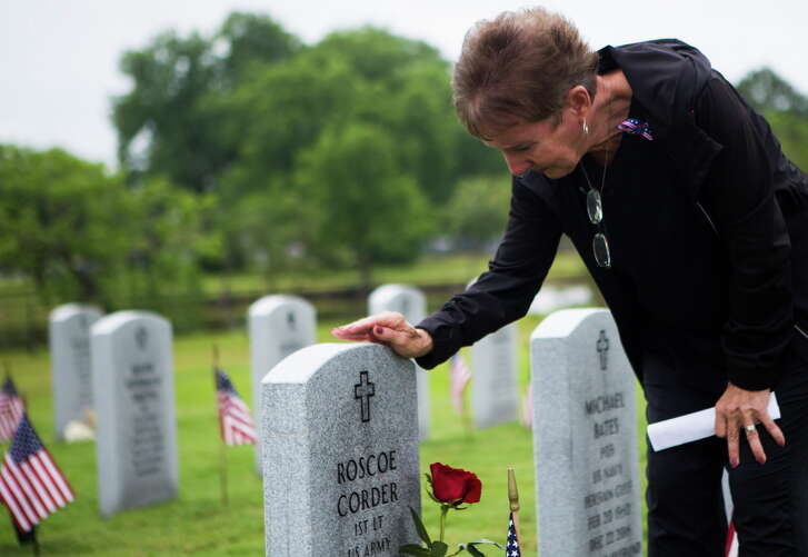 Kathy Bailey of Pasadena gently touches her father's tombstone at the Houston National Cemetery on Memorial Day, Monday, May 29, 2017.