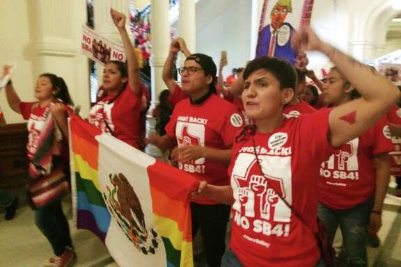 "Demonstrators march in the Texas Capitol on Monday, May 29, 2017, protesting the state's newly passed anti-sanctuary cities bill in Austin, Texas. Opponents call Texas' anti-sanctuary cities law a ""show your papers"" law since it empowers police to inquire about peoples' immigration status during routine interactions such as traffic stops. (AP Photo/Meredith Hoffman)"