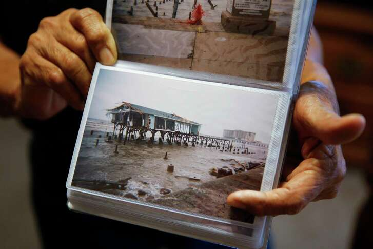 Eulalio Ojeda holds a photo he took of the seawall after Hurricane Ike Monday, May 22, 2017 in Galveston.
