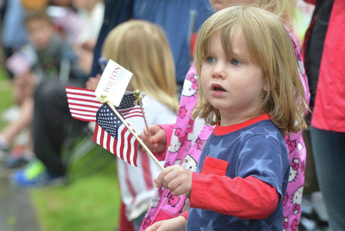 Jax Lewis waves the flag as marchers approach during the Wilton Memorial Day Parade on Monday.
