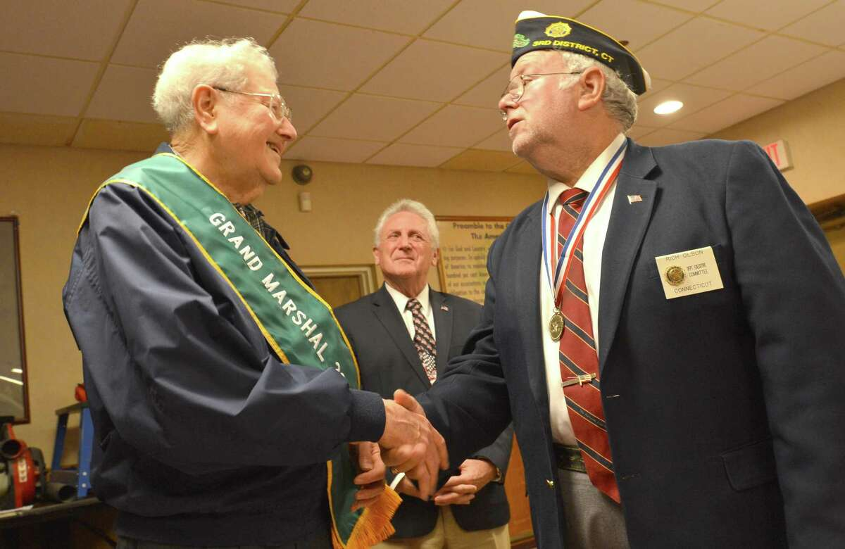 Norwalk's 2017 Memorial day parade Grand Marshal Henry Simon is recognized and given his sash during a presentation at American Legion Post 12 on Monday. Norwalk Mayor Harry Rilling spoke and Post Commander Rich Olson congratulates Simon at a the traditional lunch that is served at the post after the parade, but the parade was canceled due to bad weather.