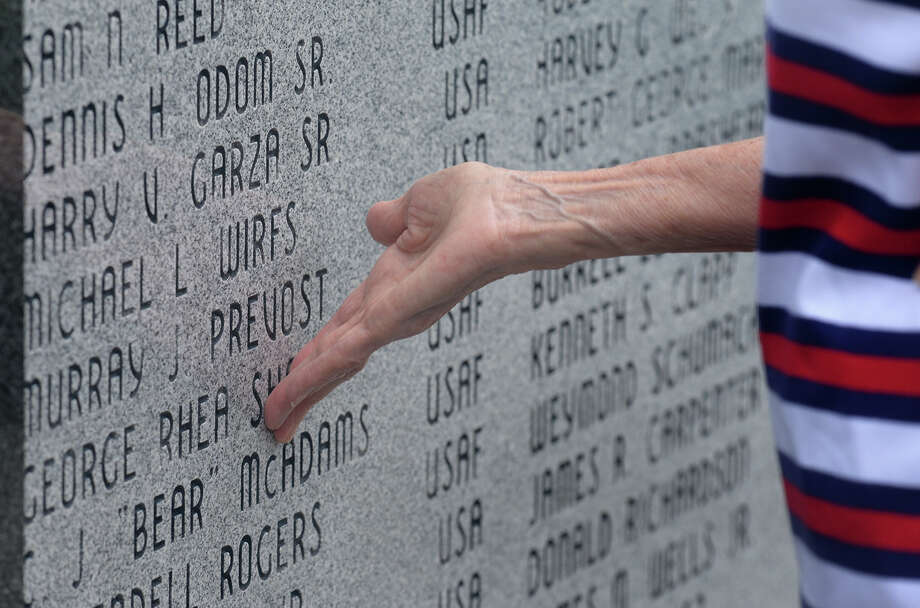 Jan Sharp touches her husband's name on veteran's wall before the Memorial Day services at Forrest Lawn on Monday. Sharp said her husband served in World War II and later for the local burial detail for military veterans. Photo taken Monday, May 29, 2017 Guiseppe Barranco/The Enterprise Photo: Guiseppe Barranco, Photo Editor