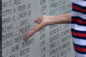 Jan Sharp touches her husband's name on veteran's wall before the Memorial Day services at Forrest Lawn on Monday. Sharp said her husband served in World War II and later for the local burial detail for military veterans. Photo taken Monday, May 29, 2017 Guiseppe Barranco/The Enterprise