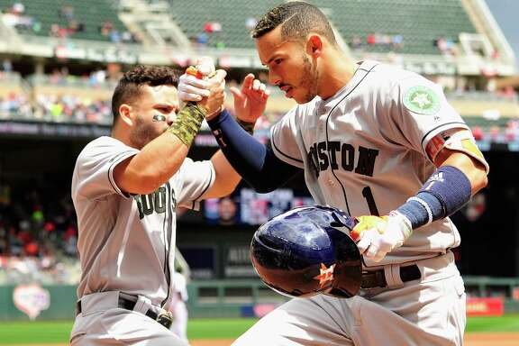 MINNEAPOLIS, MN - MAY 29: Jose Altuve #27 of the Houston Astros congratulates teammate Carlos Correa #1 on solo home run against the Minnesota Twins during the fourth inning of the game on May 29, 2017 at Target Field in Minneapolis, Minnesota.