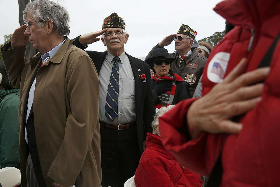 Vietnam veteran Bob Hansen (middle left) and Chuck Paskerian (middle right) salute during the 21-gun salute from the Presidion cannons after the memorial day ceremony at the Presidio cemetery on Monday, May 29 , 2017,  in San Francisco, Calif. Photo: Liz Hafalia, The Chronicle