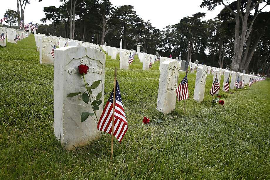Six thousand roses and lilies are placed on tombstones at the Presidio cemetery for Memorial Day. Several hundred people gathered for the ceremony honoring the dead. Photo: Liz Hafalia, The Chronicle