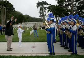 Music teacher Dan Talbert (left) leads the South San Francisco High School marching band at the Presidio cemetery before the memorial day ceremony on Monday, May 29 , 2017,  in San Francisco, Calif.