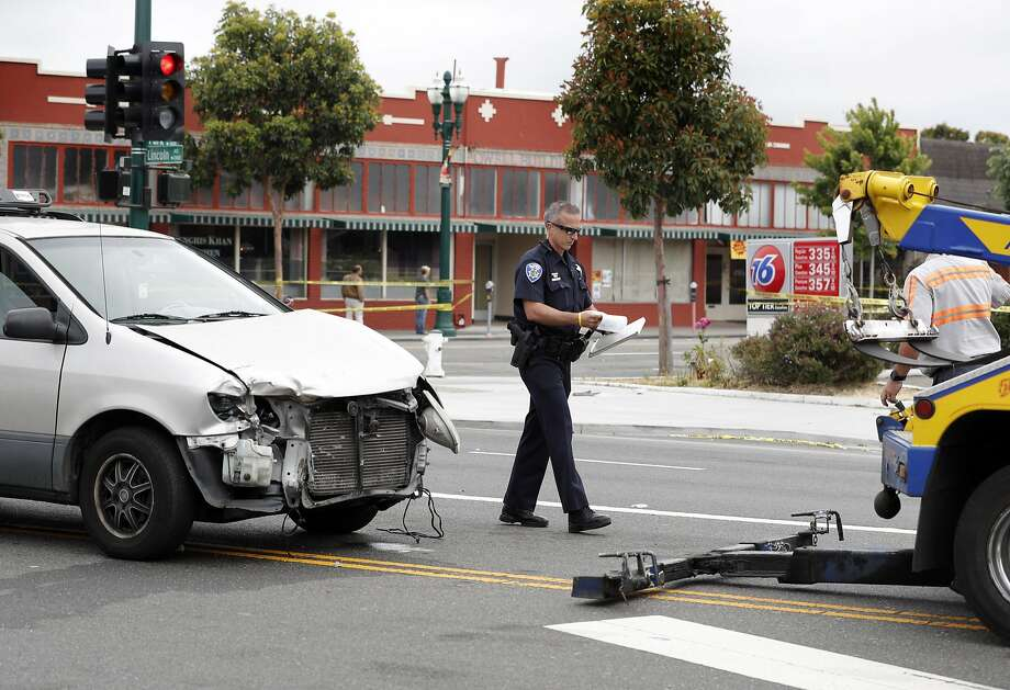 A poice officer walks by a minivan that was involved in a crash after a fatal vehicle collision in Alameda, Calif., on Monday, May 29, 2017. Photo: Carlos Avila Gonzalez, The Chronicle