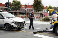 A poice officer walks by a minivan that was involved in a crash after a fatal vehicle collision in Alameda, Calif., on Monday, May 29, 2017.