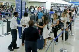 In this Friday, May 27, 2016, photo, travelers stand in line as they prepare to be screened at a Transportation Security Administration checkpoint at Fort Lauderdale-Hollywood International Airport in Fort Lauderdale, Fla. By air or car, summer 2017 travel numbers are expected to rise over the previous year thanks to deals on airfares and stable gasoline prices. (AP Photo/Alan Diaz) ORG XMIT: NYBZ530