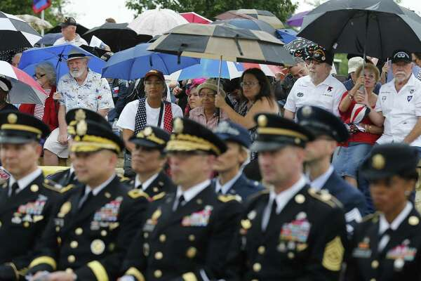 Some of the 1,000-plus attendees at the ceremony get under umbrellas as rain falls during the ceremony.