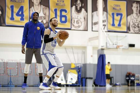 Stephen Curry makes a shot as Kevin Durant watches during practice at the Warriors headquarters in Oakland, Calif., on Monday, May 29, 2017.