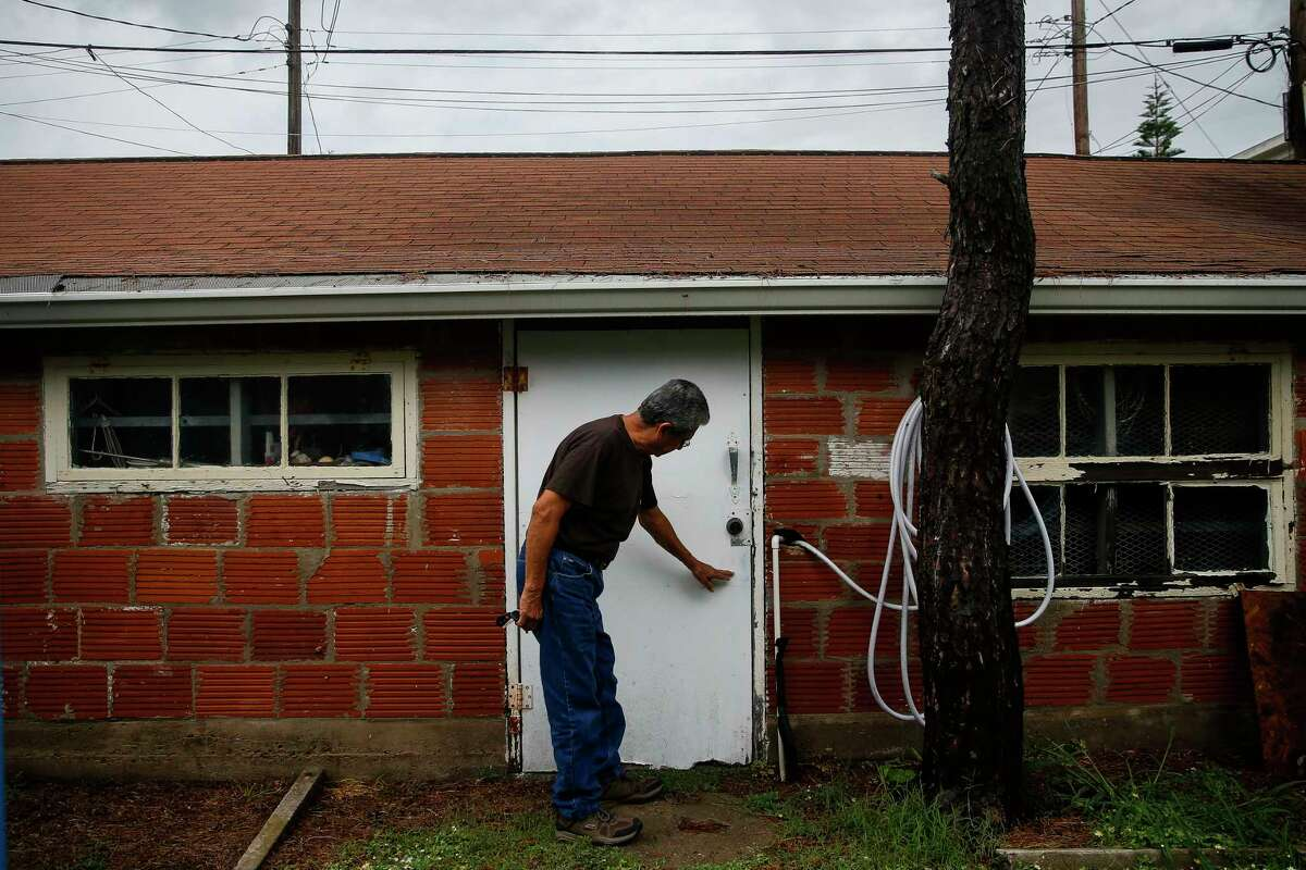 Lalo Ojeda points to the water line on his garage in Galveston from Hurricane Ike in 2008.