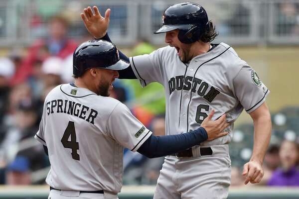 George Springer, left, and Jake Marisnick celebrate after scoring the sixth and seventh runs in the Astros' 11-run eighth inning Monday.