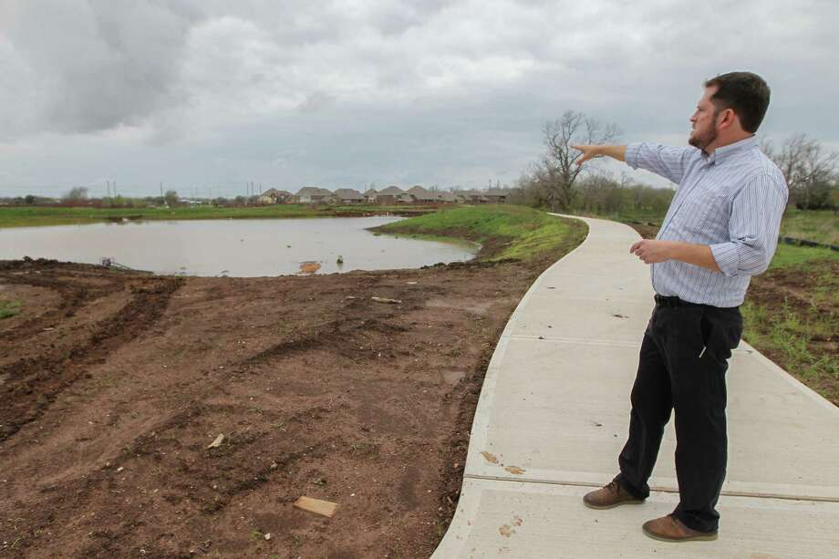 TBG Partners Principal Meade Mitchell points to areas of at a wetland park in the Riverstone Development, Tuesday, March 7, 2017, in Sugar Land. Developers say master planned communities are trending away from fancy amenities and towards vibes of authenticity and connection with the land. Good bye to golf courses and swimming pools, hello to urban farm plots, natural waterways and wild space. Wetland Park, which will be wetland themed in homage to its natural ancestry, with preserved wetland space and rugged-esque trails throughout. ( Steve Gonzales  / Houston Chronicle ) Photo: Steve Gonzales, Staff / © 2017 Houston Chronicle