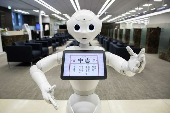 A Pepper humanoid robot stands at a Mizuho Bank branch in Tokyo. For Japan and Germany, robots are likely to step up as their labor force growth slows.