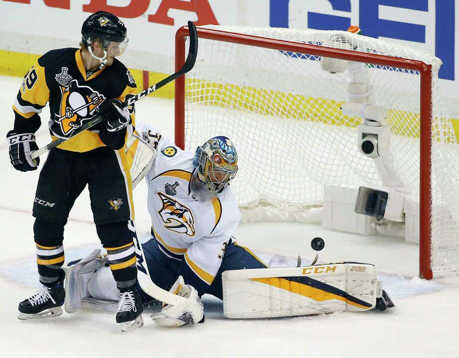 Pittsburgh Penguins' Jake Guentzel, front, watches a goal by teammate Evgeni Malkin in front of Nashville Predators goalie Pekka Rinne during the first period in Game 1 of the NHL hockey Stanley Cup Final, Monday, May 29, 2017, in Pittsburgh. (AP Photo/Gene J. Puskar) ORG XMIT: PAWS115 Photo: Gene J. Puskar / Copyright 2017 The Associated Press. All rights reserved.
