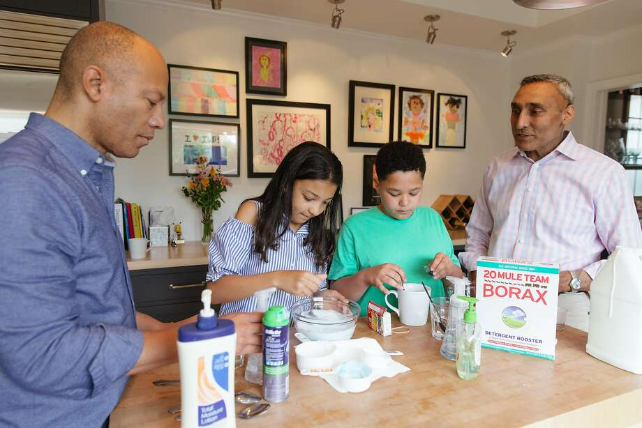 Ken McNeely, president of AT&T California, and his husband, Dr. Inder Dhillon, are guided by their kids, Meera and Kabir, in making slime at their S.F. home. Photo: Peter Prato, Special To The Chronicle