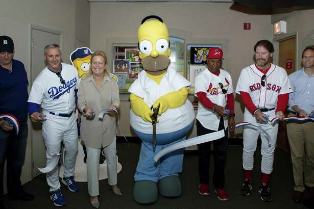 Homer Simpson cuts a ceremonial ribbon Saturday at the National Baseball Hall of Fame and Museum in Cooperstown, N.Y. Pictured from left are Al Jean, Steve Sax, Hall of Fame Chairman Jane Forbes Clark, Homer Simpson, Ozzie Smith, Wade Boggs and Hall of Fame President Jeff Idelson.