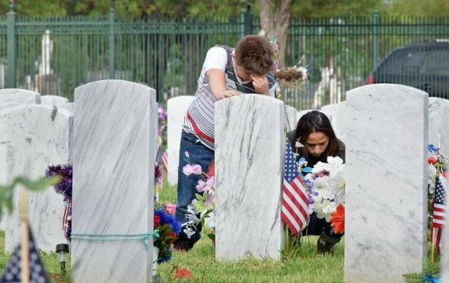 Domingo and Isa Saldana reflect at the tombstone of their late father Army Vietnam War veteran Guadalupe Saldana during the Memorial Day Observance held at the City Cemetery Monday. Photo: Ulysses S. Romero/Laredo Morning Times