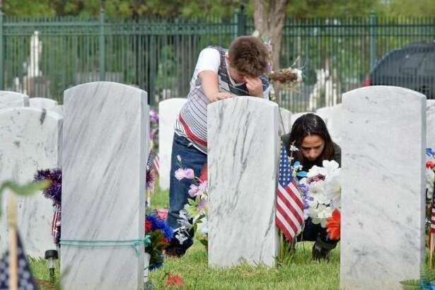 Domingo and Isa Saldana reflect at the tombstone of their late father Army Vietnam War veteran Guadalupe Saldana during the Memorial Day Observance held at the City Cemetery Monday.
