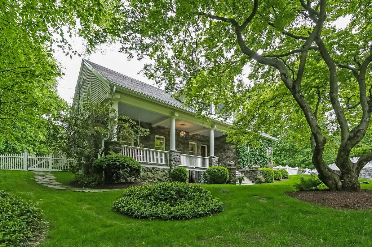 The updated antique farmhouse has a long, covered front porch and it sits on a level and sloping property of just under an acre in the Tokeneke neighborhood.