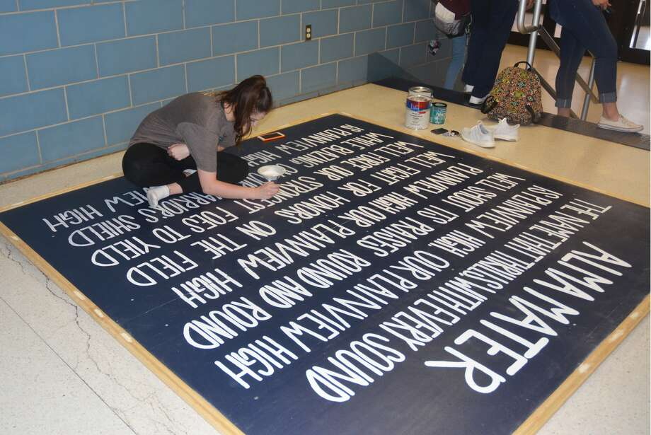 Lauren Pritchard paints the words to the Plainview High School alma mater on a sign in a hallway outside the PHS gym. The completed sign will hang inside the varsity gymnasium. Pritchard played basketball for the Lady Bulldogs as a junior last season.