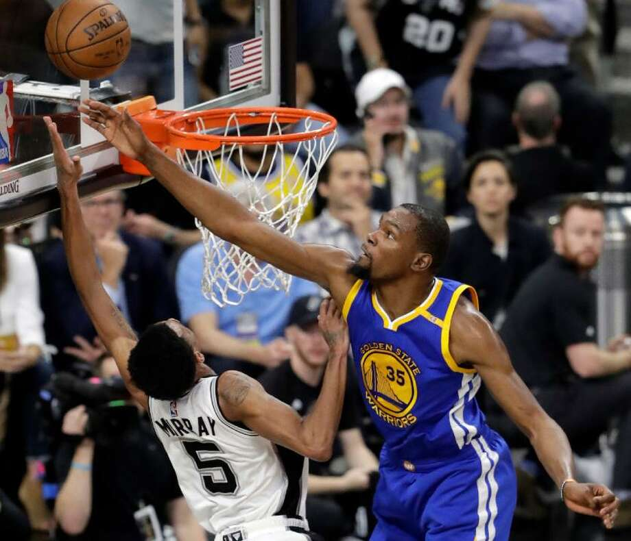 Spurs guard Dejounte Murray (5) has his shot blocked by Golden State Warriors' Kevin Durant (35) during the first half in Game 4 of the Western Conference finals on May 22, 2017, in San Antonio. Photo: Eric Gay /Associated Press