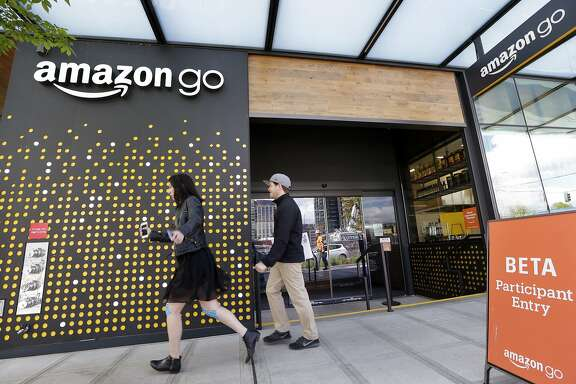 FILE - In this Thursday, April 27, 2017, file photo, people walk past an Amazon Go store, currently open only to Amazon employees, in Seattle. Amazon Go shops are convenience stores that don't use cashiers or checkout lines, but use a tracking system that of sensors, algorithms, and cameras to determine what a customer has bought. Wal-Mart�s acquisition of Jet.com is accelerating its progress in e-commerce as it works to narrow the gap between itself and online leader Amazon. Wal-Mart is betting its online future on essentials like produce and groceries and has adjusted its shipping strategy. But Amazon keeps innovating too. (AP Photo/Elaine Thompson, File)