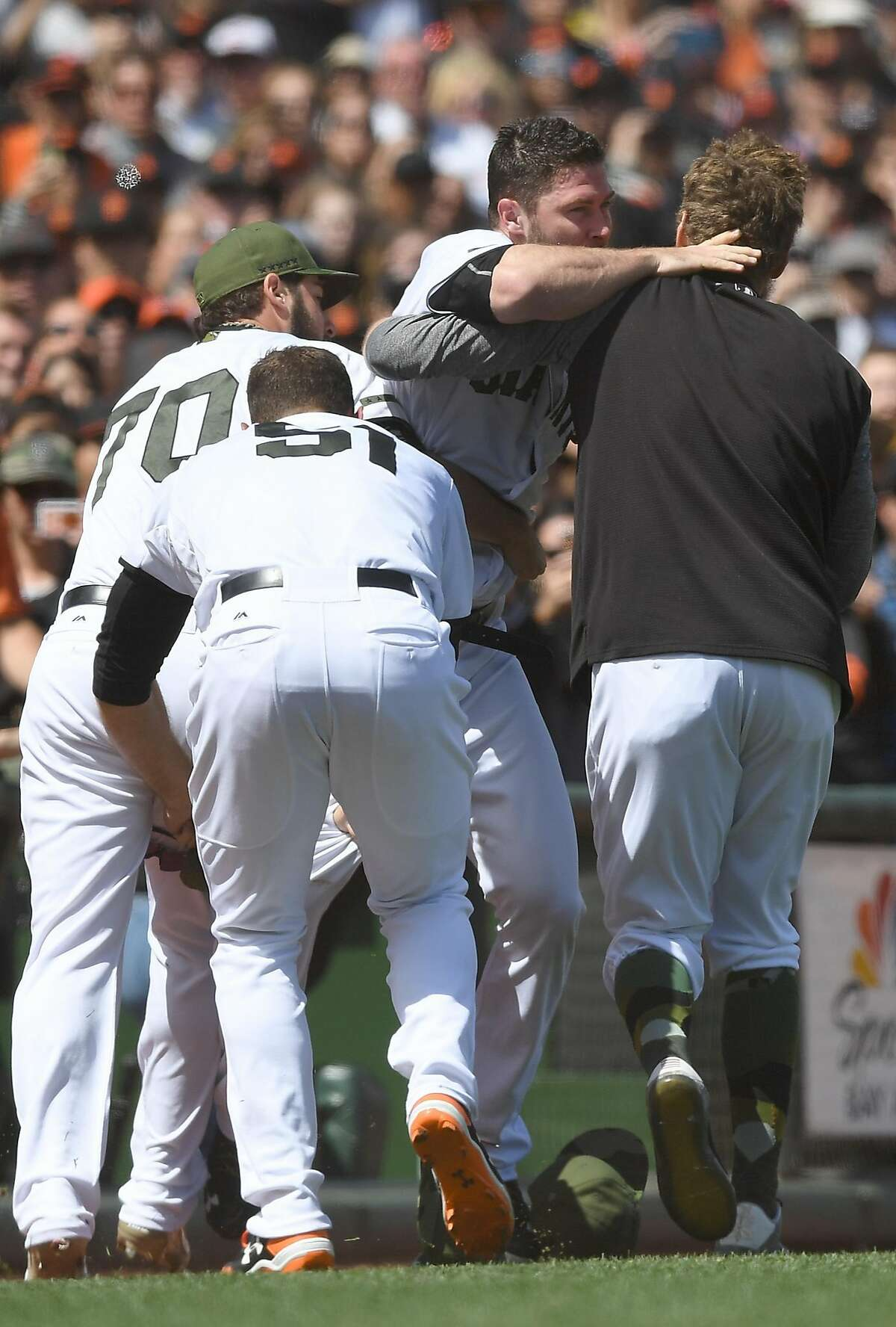 SAN FRANCISCO, CA - MAY 29: Hunter Strickland #60 of the San Francisco Giants gets carried off the field by three teammates (L-R) George Kontos #70, Mac Williamson #51 and Hunter Pence #8 after Strickland got into a fight with Bryce Harper #34 of the Washington Nationals after he hit Harper with a pitch in the top of the eighth inning at AT&T Park on May 29, 2017 in San Francisco, California. (Photo by Thearon W. Henderson/Getty Images)