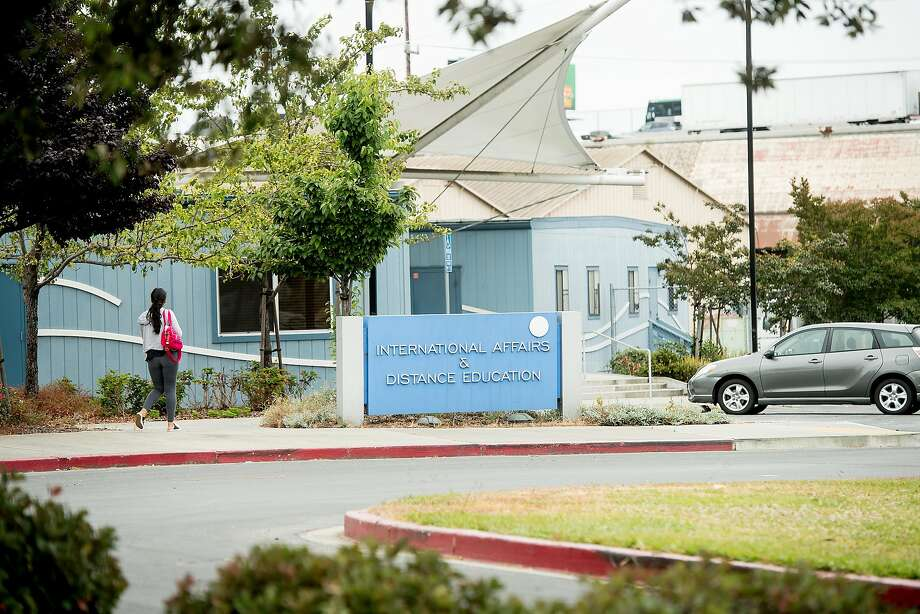 A pedestrian passes a building at the Peralta Community College District offices, one of three sites under consideration for a new Oakland Athletics baseball stadium. Photo: Noah Berger, Special To The Chronicle